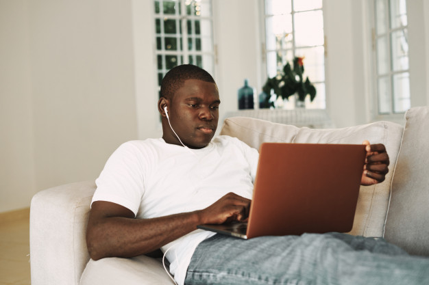 african american man working at home with laptop