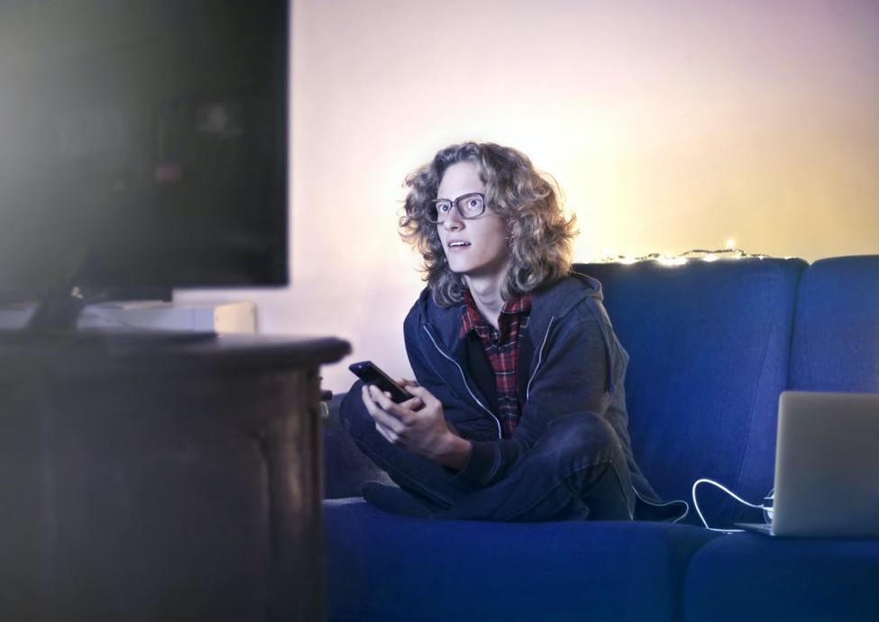 Man using smartphone watching TV