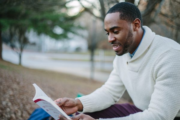 man in a sweater reading a book